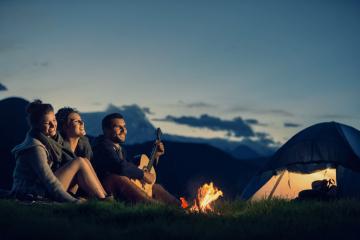 traveler am Lagerfeuer mit Gitarre und Zelt. Auf dem Bild sind drei Freunde zu sehen, die am Lagerfeuer sitzen, eine gute Zeit haben und Musik machen. Es ist abends und es ist eine romantische Stimmung. Im Hintergrund ist ein Zelt zu sehen.