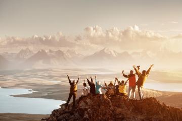 traveler in den Bergen. Auf dem Bild ist eine Reisegruppe zu sehen, die den Gipfel eines Berges erreicht hat. Alle Reisenden sind sehr glücklich und strecken ihre Arme aus. Im Hintergrund sind weitere hohe Berge und ein See zu sehen. Außerdem ist gerade Sonnenaufgang