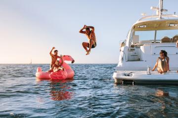 Freunde haben eine gute Zeit auf einem Boot. Auf dem Bild sind fünf Personen zu sehen, die Spaß haben. Zwei der Personen sitzen auf einem Boot, einer sringt gerade ins Wasser und zwei sitzden gerde auf einem aufblasbaren Flamingo