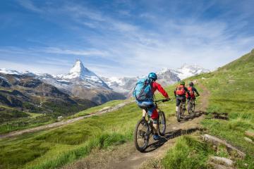 Radfahren in den Bergen. Auf dem Bild sind drei Personen zu sehen, die mit Rucksack in den Bergen auf ountainbikes unterwegs sind. Sie tragen alle einen Helm.