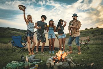 Freunde haben eine gute Zeit. fünf Freunde stehen auf einer Wiese. sie trinken und tanzen und sie sind glücklich. Sie stehen vor einem Lagerfeuer,außerdem ist ein Campingzelt zu sehen