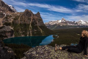 Wandern in Kanada. Eine junge Frau sitzt mit Wanderschuhen auf einem Felsen. Im Hintergrund sind Berge zu sehen, die teilweise mit Schnee bedeckt sind. Auch ist ein See zu sehen.
